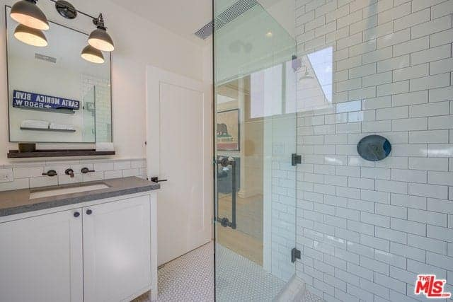 The frame-less vanity mirror is topped with a couple of Farmhouse-style wall-mounted lamps that cast down warm yellow lights over the gray countertop of the white wooden vanity next to the glass door of the shower area that has white wall tiles.