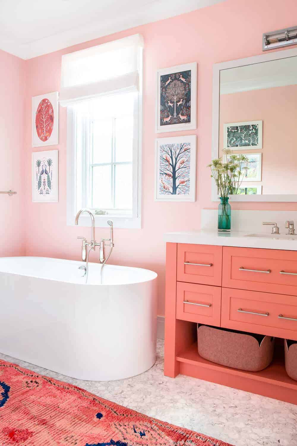 This is a beautiful chic bathroom that has various shades of pink scattered everywhere. It has a pink area rug, pink wooden vanity and light pink walls that rare adorned with framed artworks mounted above the freestanding bathtub by the window.