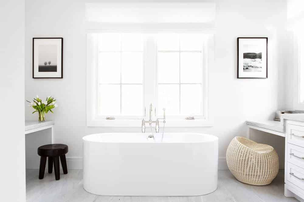 The bright French windows bring in an abundance of natural lights that lighten up the white walls accented with framed artworks. It also lightens up the white vanity and freestanding bathtub adorned with a rustic woven basket chair beside it.