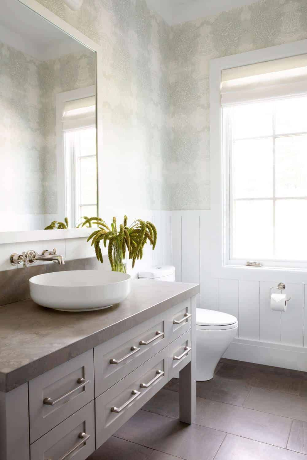 The light gray upper walls are a good match for the gray countertop and the flooring tiles of this bathroom. These are all brightened by the white wooden wainscoting that has a Farmhouse-style finish to it.