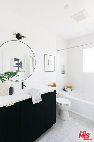This simple Farmhouse-style bathroom has a bright white aura to it due to the white walls, ceiling and the light gray flooring that are all further brightened by the abundant natural lighting coming in from the window above the bathtub. This is contrasted by the dark floating vanity.