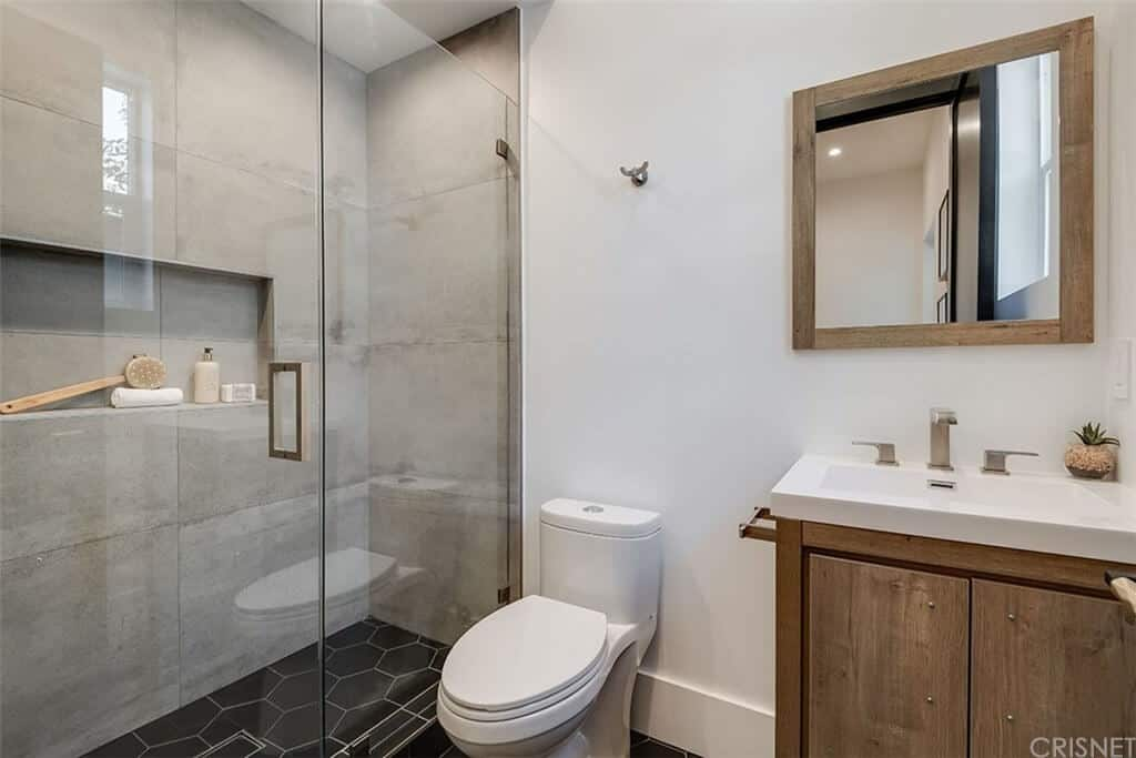 The white porcelain toilet stands out against the black hexagonal floor tiles as it stands in between the wooden vanity with a wooden wall-mounted mirror and the glass enclosed shower area that has gray wall tiles that look like concrete.