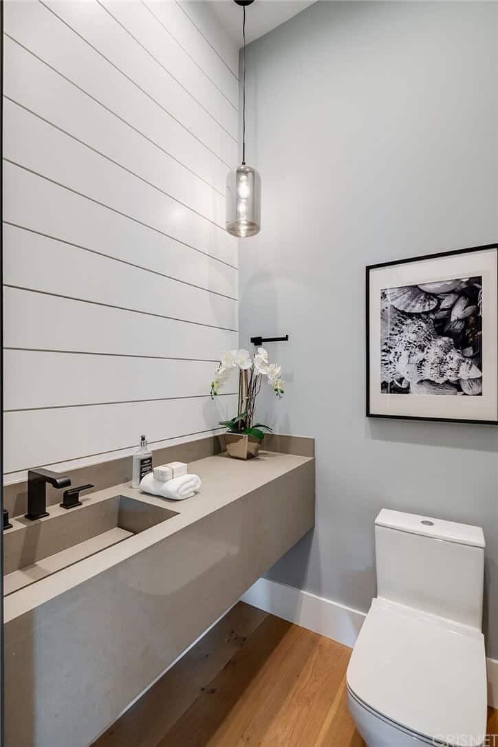 The simplicity of this Farmhouse-style bathroom stems from its hardwood flooring, light gray walls and a simple white porcelain toilet. This is augmented by the sleek gray floating vanity with a modern sink that complements the white wall with a wooden plank finish.