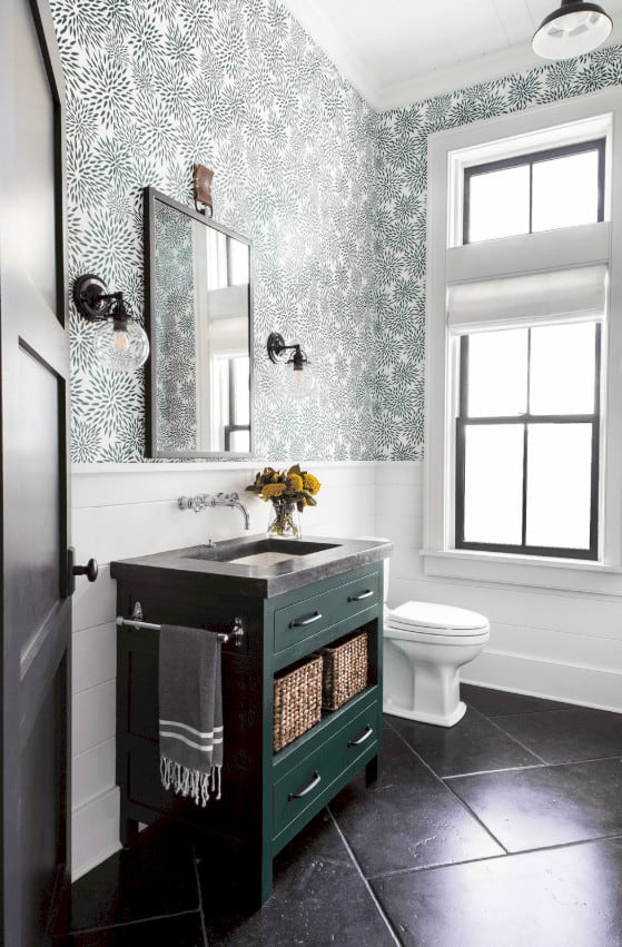The green wooden vanity has drawers and a shelf for baskets. This complements the black tiles of the floor that contrast the white toilet and the white wainscoting of the walls brightened by the natural lights coming in from the tall window beside the toilet.