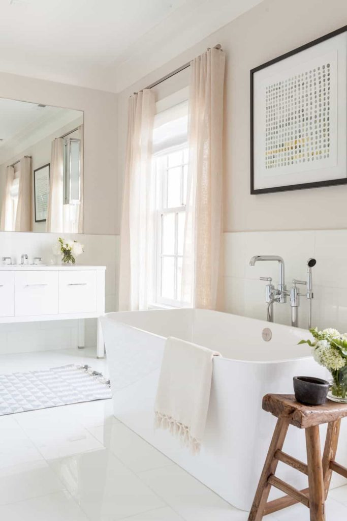 The bright natural lights that are coming in from the pink curtained window brightens up the white wooden cabinets of the vanity, the white tiles of the flooring and the white freestanding bathtub adorned with a small wooden stool beside it that serves as a table.