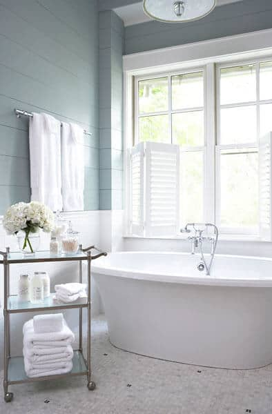 The beautiful shuttered windows above the white freestanding bathtub has a brightness to it that stands out against the gray wooden walls with a shiplap plank finish. Beside the bathtub is a wheeled trolley that serves as a towel storage and also for decors.
