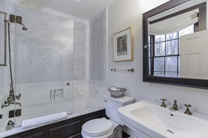 The bathtub is inlaid with a black wooden housing that makes the white porcelain toilet stand out. This black element matches with the frame of the vanity mirror that is mounted on the white wall above the white sink.