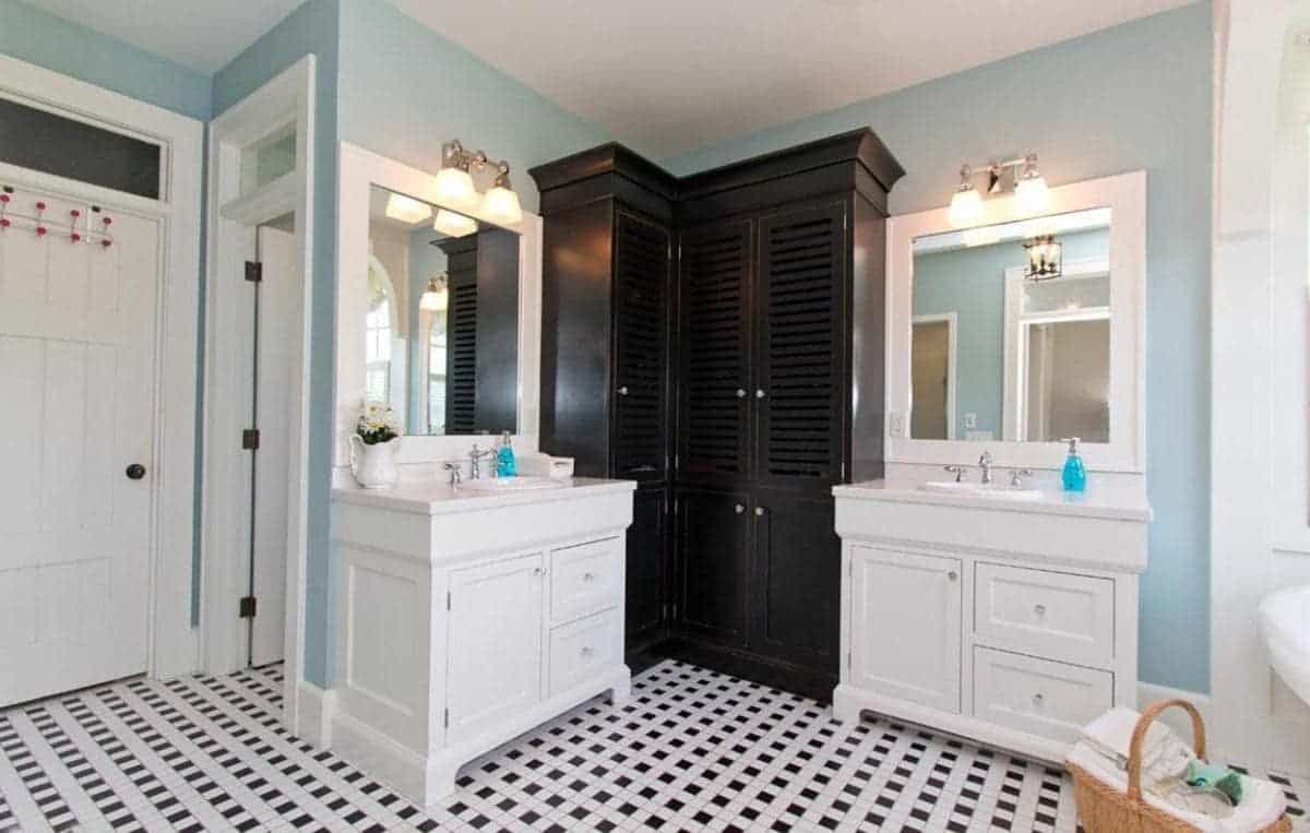 This is the vanity area beside the white bathtub on the right side. It has two separate white wooden structures that has cabinets, drawers and houses a white sink and a vanity mirror above it. In between these two vanities is an L-shaped black wooden cabinet for storage.