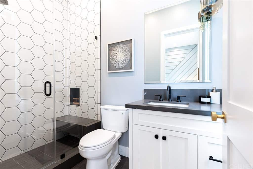 The white hexagonal tiles of the shower area walls makes the shower area stand out along with the white porcelain toilet and the white wooden vanity against the black tiles of the flooring. This contrast is augmented by the white lights shining down from the ceiling.