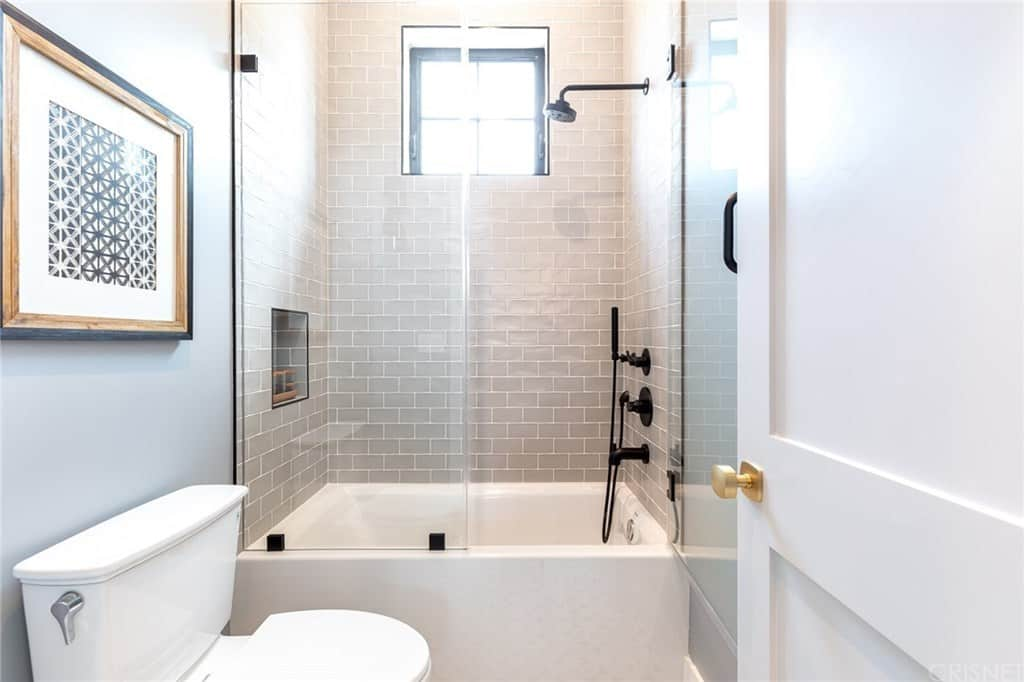 The white toilet stands out against the light blue wall behind it adorned with a framed artwork mounted above the toilet. Next to this is the bathtub that also doubles as the glass-enclosed shower area with light gray tiles on the walls contrasted by the black fixtures.