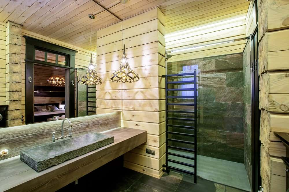 The large stone basin of the sink is a great match for the gray stone walls of the shower area behind the tinted glass door. This also matches with the flooring tiles that are contrasted by the wooden walls and ceiling that are augmented by the warm yellow lights of the decorative pendant light.