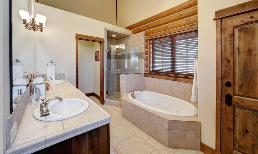 There is a wooden two-sink vanity that has the same beige tiles on its countertop as the flooring and the those enclosing the bathtub as well as the glass-enclosed shower area. These are complemented by the wooden elements of the door and the frame of the window above the bathtub.