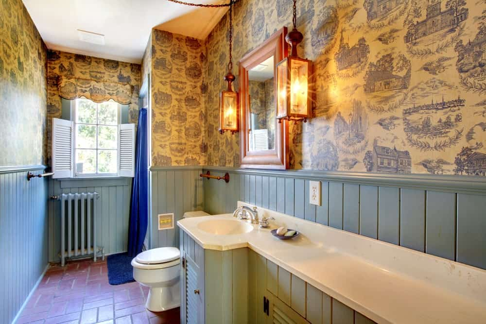 The upper walls of this Farmhouse-style bathroom is dominated by an ember wallpaper with charming images of houses on it. This is paired with light gray wooden wainscoting that blends with the vanity and the shuttered windows on the far wall.