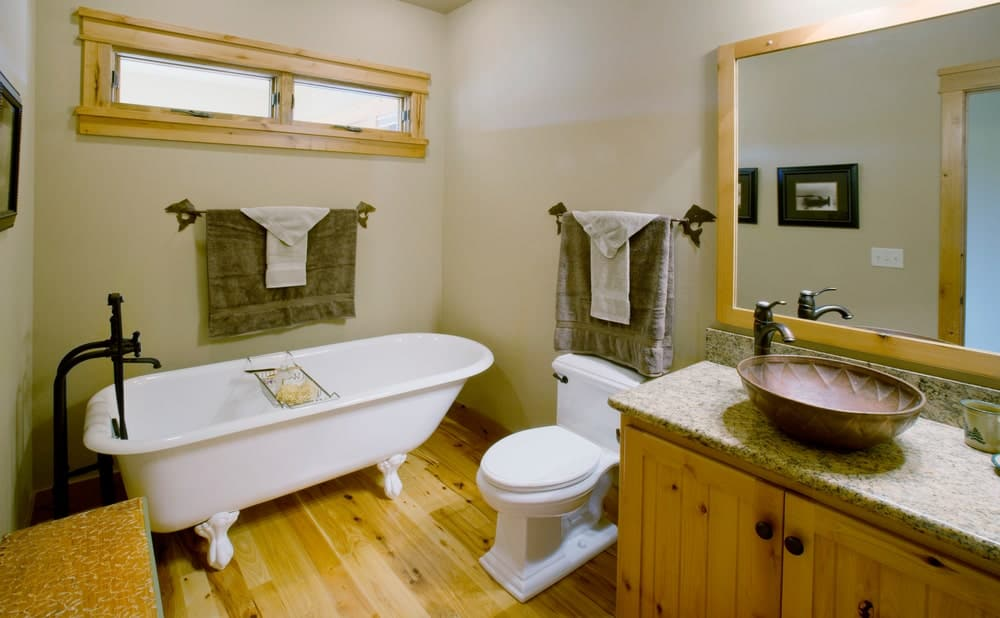 The hardwood flooring of this bathroom matches with the wooden vanity cabinets and the frames of the vanity mirror as well as the narrow window above the freestanding bathtub beside the white toilet.