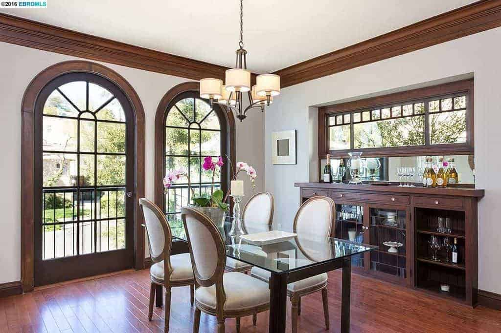 The hardwood flooring of this medium-sized dining room matches with the frames of the arched glass doors that bring in an abundance of natural lights to the glass-top dining table paired with white cushioned oval back chairs that stand out against the flooring and dining room cabinet embedded into the white wall.