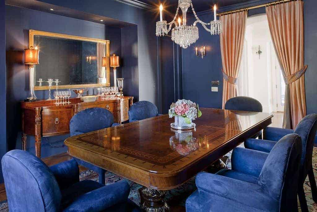 The blue walls of this medium-sized dining room blend with the blue velvet cushions of the armchairs that encircle the wooden dining table that matches the console table. The dining table is adorned with a simple crystal chandelier hanging from the blue ceiling.