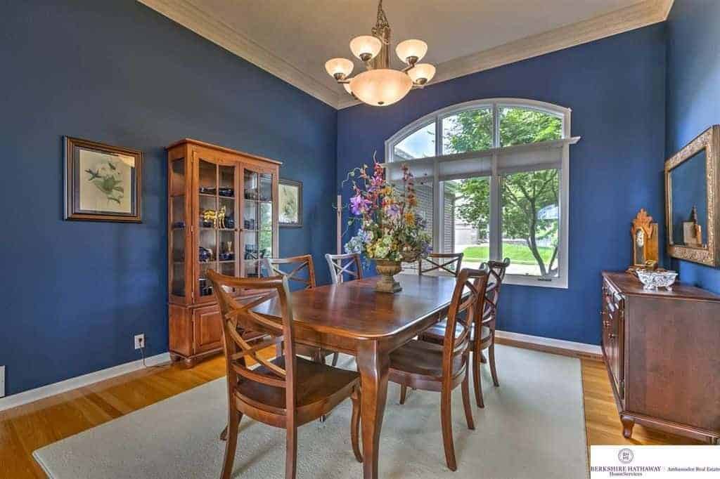 The charming blue walls are brightened and enhanced by the large arched window that brings in natural lighting that augments the warm chandelier over the wooden dining table that matches with the cabinet and hardwood flooring topped with a light gray area rug.