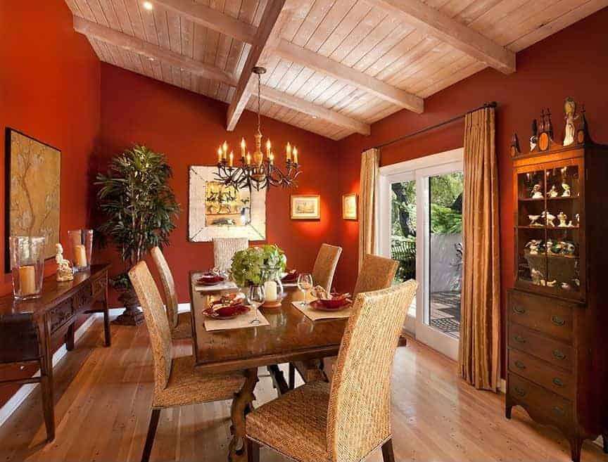 The wooden shed ceiling of this medium-sized dining room has exposed wooden beams matching with the hardwood flooring. These are contrasted by the earthy red tone of the walls that complements the dining room cabinet, console table and dining table perfectly paired with rustic woven wicker Parson's chairs.