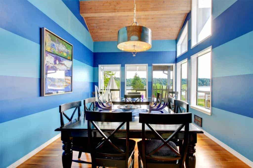 The delightful blue-striped walls offers a bright and cheerful contrast to the traditional dark wooden table and its wooden cross back chairs that complement the hardwood flooring. These are all brightened by the natural lights coming from the windows.
