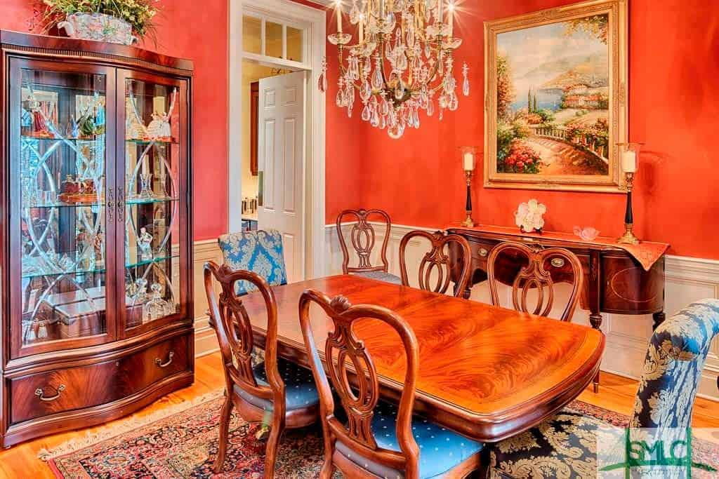 The orange walls of this elegant and chic dining room sets a nice background for the traditional elements of the wooden dining table and chairs that match with the dining room cabinet with glass panels that pair nicely with the crystal chandelier.