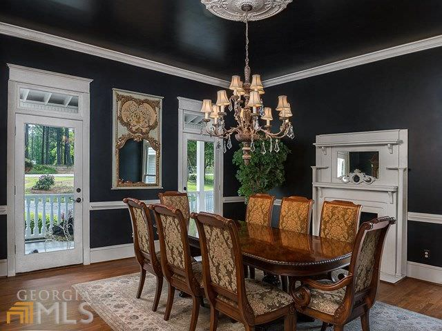 This medium-sized dining room still manages to be bright despite its black walls and ceiling. This is due to the abundance of natural lighting that comes in through the two glass doors flanking a wall-mounted mirror that faces the wooden dining table and its wooden chairs with floral cushions.