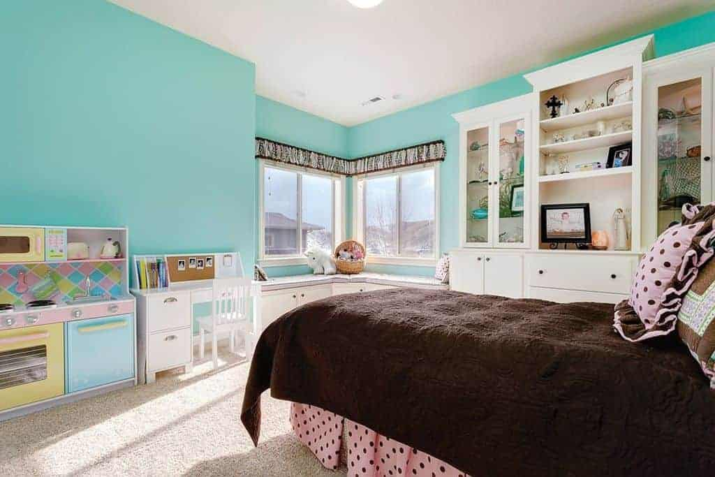 Aqua bedroom offers a skirted bed wrapped in a cozy brown blanket along with a built-in cabinet and window seat nook over carpet flooring.