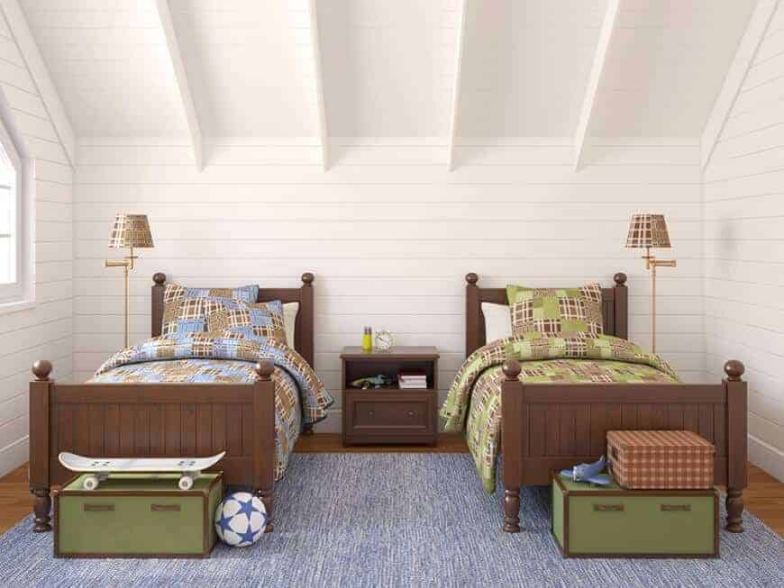 Shared kids bedroom with shiplap walls and hardwood flooring topped by a blue rug. It has green storage boxes and a wooden nightstand situated in between the beadboard beds and floor lamps which create symmetry in the room.