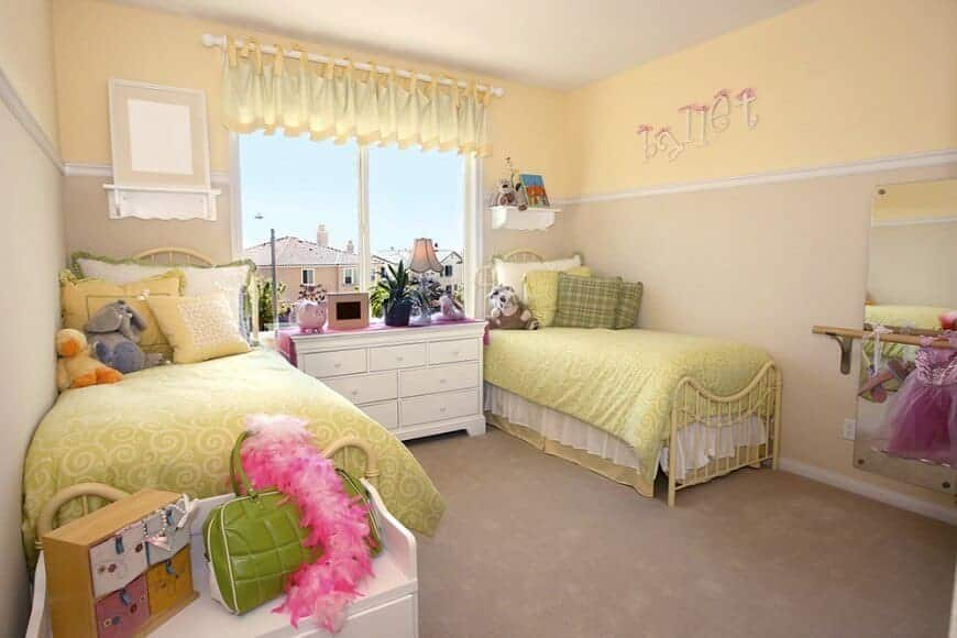 Bright bedroom features metal beds and a white drawer chest placed against the glazed windows covered in yellow valance. It has carpet flooring and two-tone walls mounted with floating shelves and a frameless mirror.