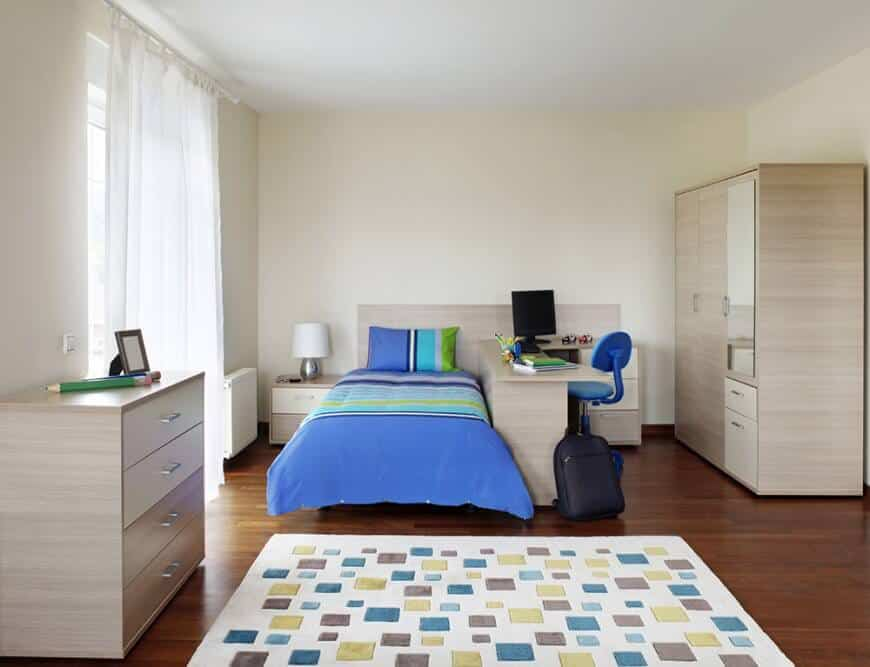 Boy's bedroom with an eye-catching patterned rug and a built-in bed in light wood integrated with a desk that's accompanied by a blue swivel chair.