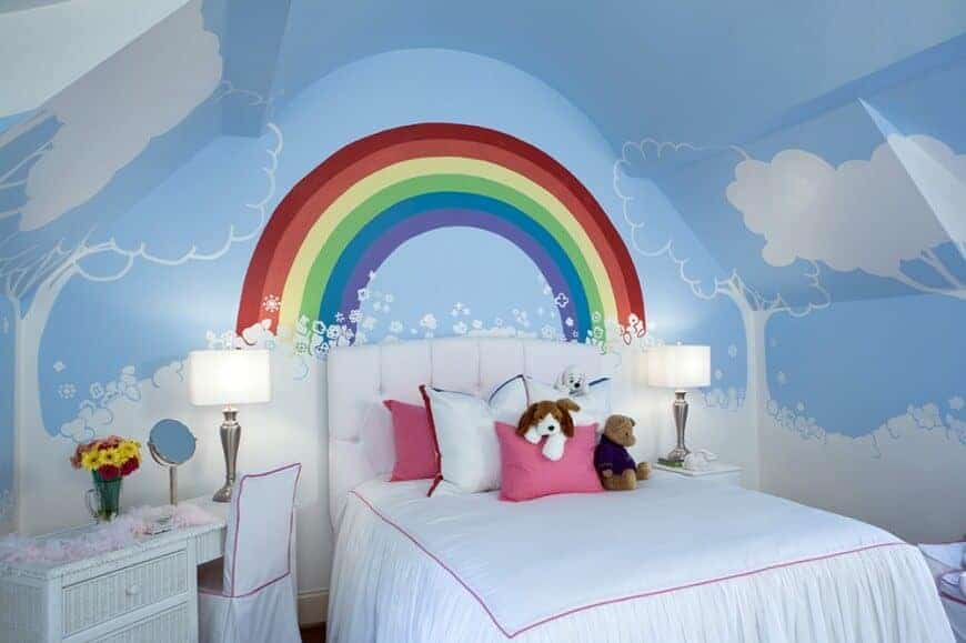 A rainbow mural adds a charming accent in this girl's bedroom with a white tufted bed and beadboard desk topped with a chrome table lamp.
