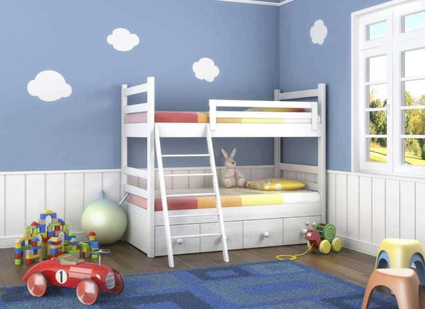 Boy's bedroom clad in sky wallpaper and white beadboard complementing with the bunk bed and framed window. It has multicolored chairs and a blue rug that lays on the wide plank flooring.