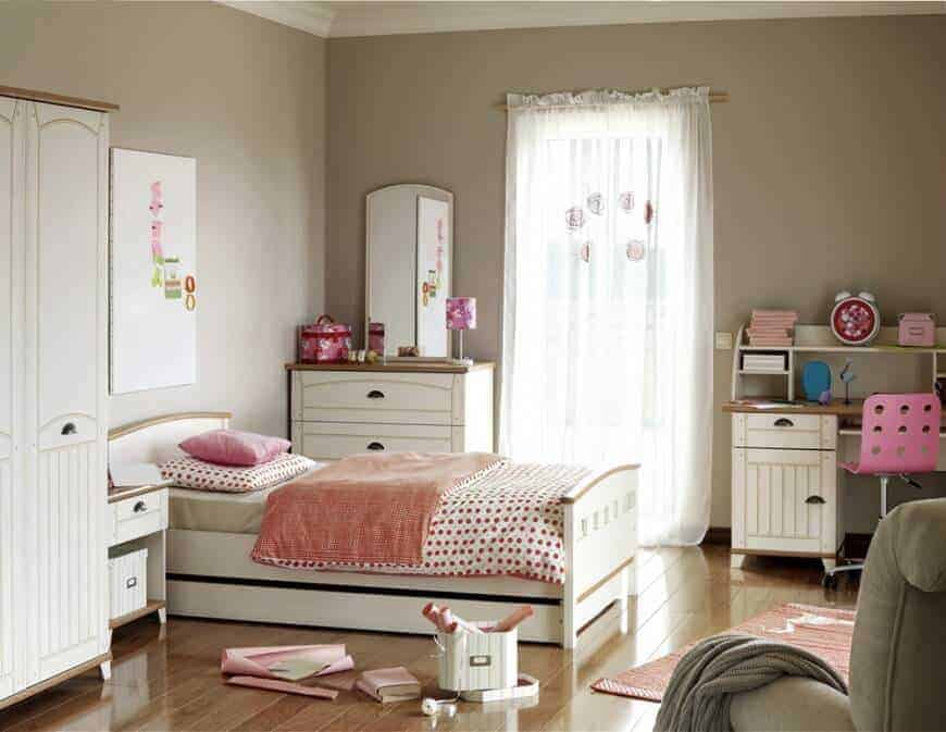 A pink perforated swivel chair sits at a white desk in this beige bedroom filled with wooden bed and cabinets over wide plank flooring.
