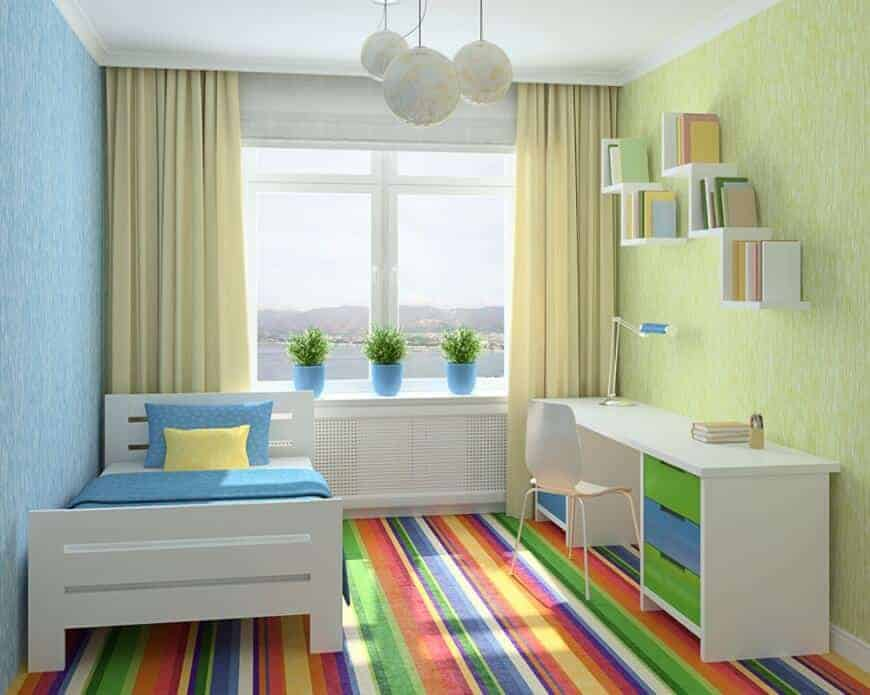 Kids bedroom illuminated by globe pendants along with natural light from the glazed windows covered in yellow drapes. It has a white bed and desk accented with a colorful striped carpet.
