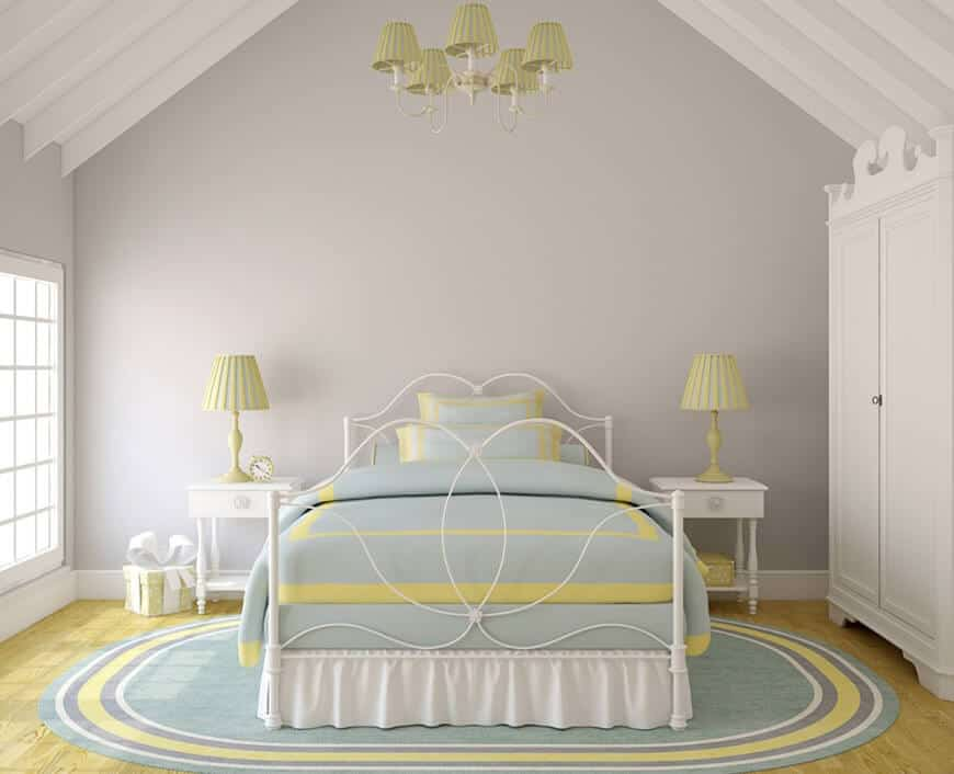 Classy bedroom features a gorgeous metal bed on an oval rug lighted by pleated shade chandelier and matching table lamps that sit on white nightstands.