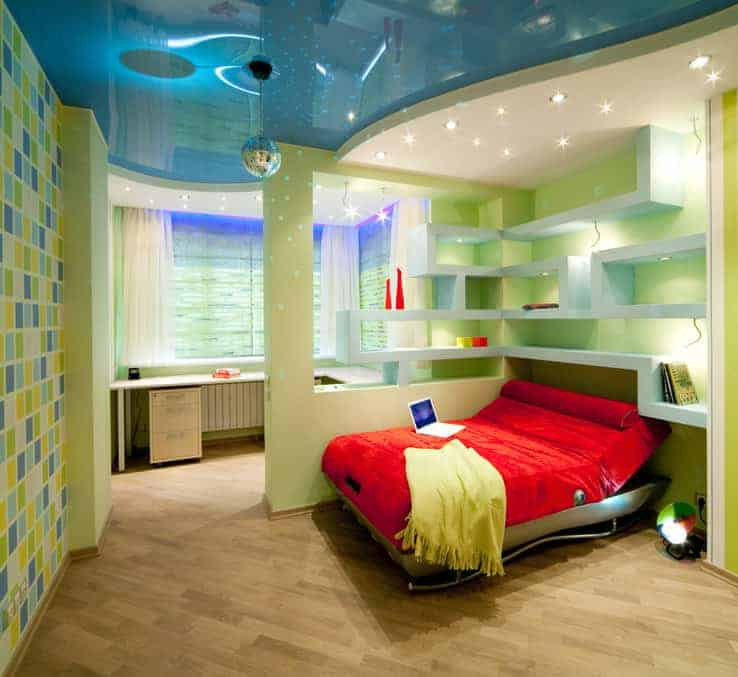 Magnificent bedroom with hardwood flooring and a stylish ceiling mounted with recessed lights and a chrome globe pendant. It has a red bed and an L-shaped desk separated by built-in shelving.