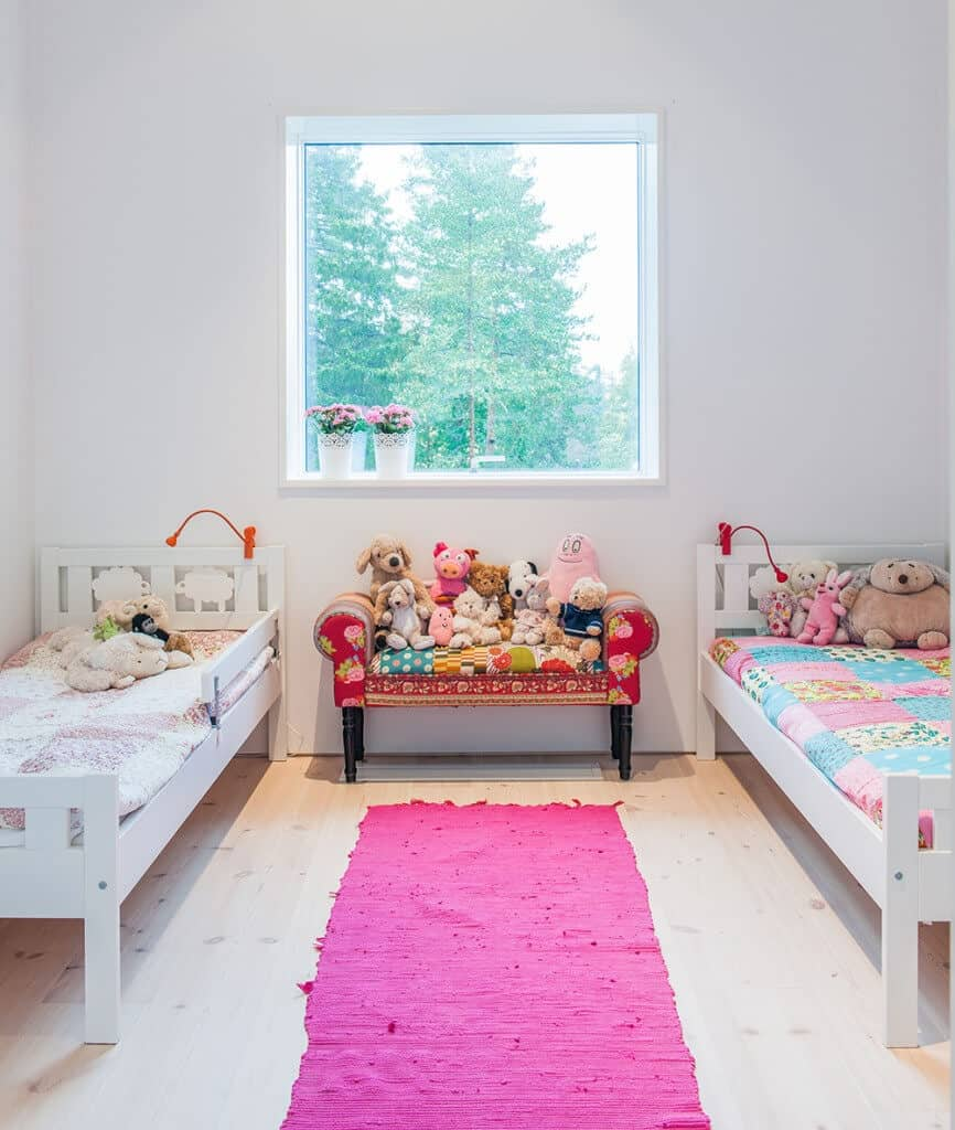 A mini red sofa filled with animal plush toys sits in between the white beds in this shared girls bedroom with a picture window and light hardwood flooring topped by a pink runner.