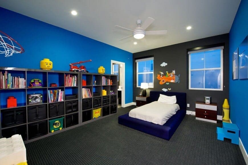 Boy's bedroom with open shelving and a deep blue platform bed illuminated by recessed lights and flush mount light integrated to the white ceiling fan.