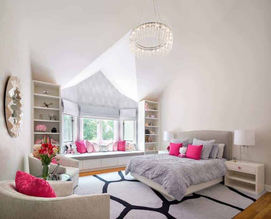 A round crystal chandelier illuminates this girl's bedroom boasting a gray bed and window seat nook filled with pink pillows. It includes white nightstands and beige round back chairs with a glass top table in the middle.