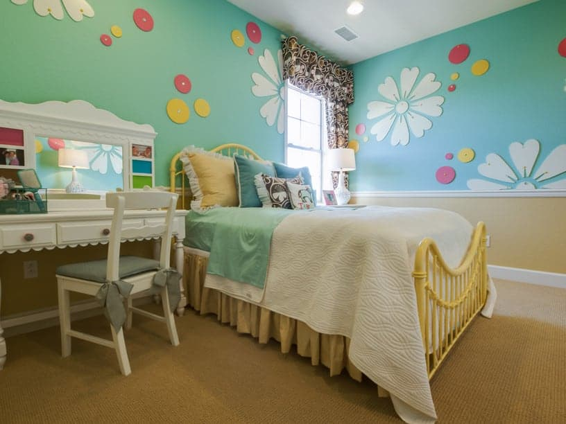 Aqua floral walls add charm in this girl's bedroom offering a yellow metal bed and a lovely desk over carpet flooring,