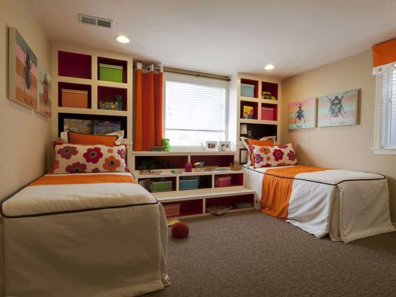 Shared kids bedroom with skirted beds and built-in shelvings filled with multicolored storage boxes. It is decorated with insect artworks mounted on the beige walls.