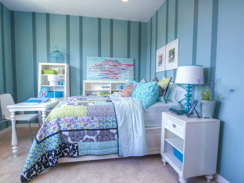 Clad in blue striped wallpaper, this bedroom showcases open shelvings and a white desk facing the comfy bed with white framed photos overhead.
