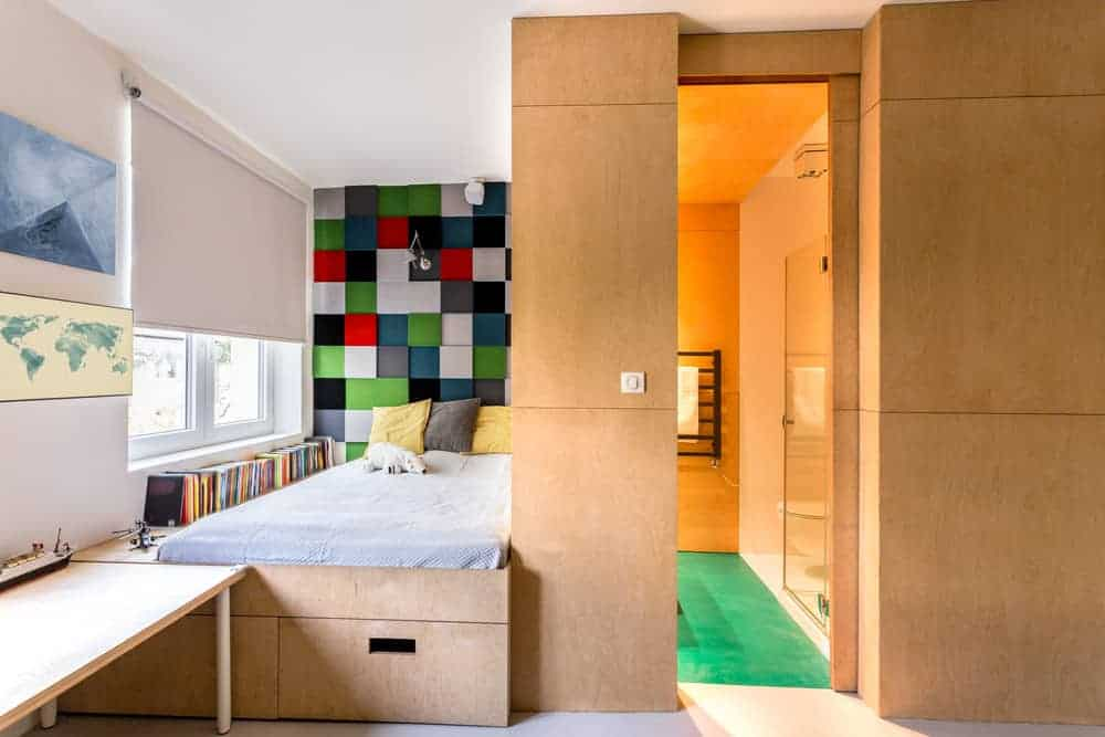 A checkered wall adds a striking accent in this kids bedroom with a built-in bed that matches the wood paneled walls and a glazed window covered in white roller blind.