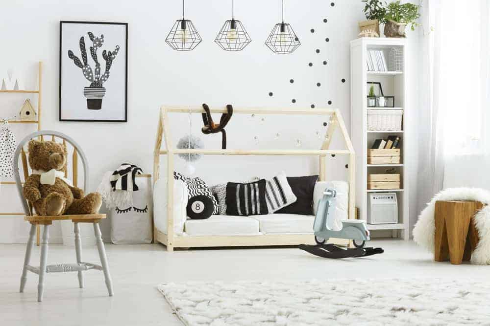 A cute teddy bear sits on the wooden round back chair in this kids bedroom featuring a canopy hut poster bed and a stylish seat covered in a white faux fur blanket.