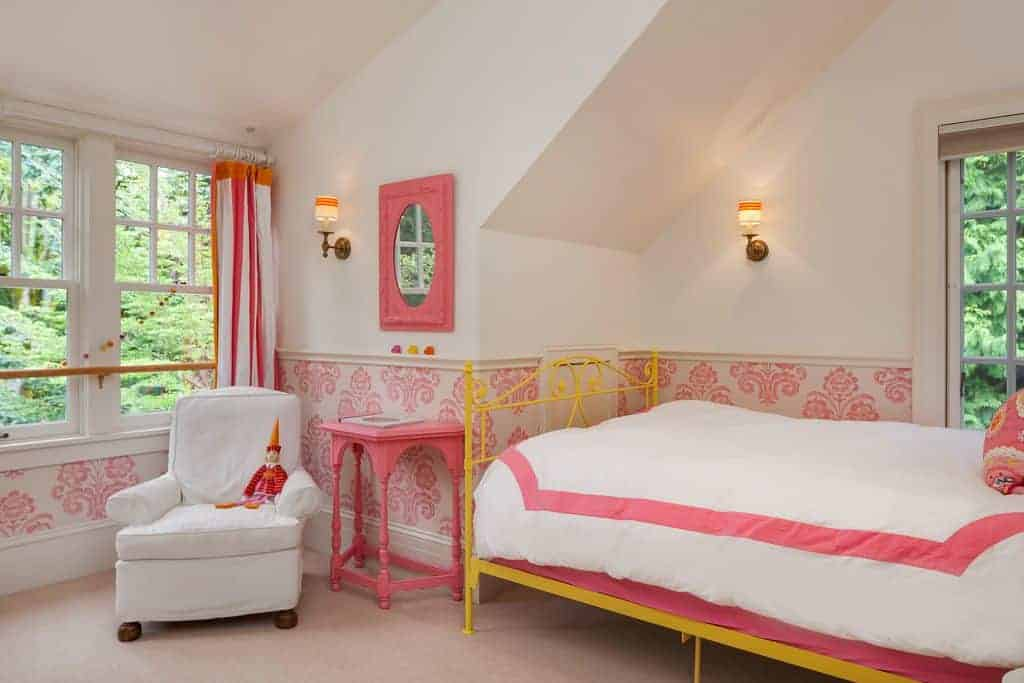 An airy bedroom showcases yellow metal bed and white skirted armchair with a pink console table in the middle paired with an ornate mirror.