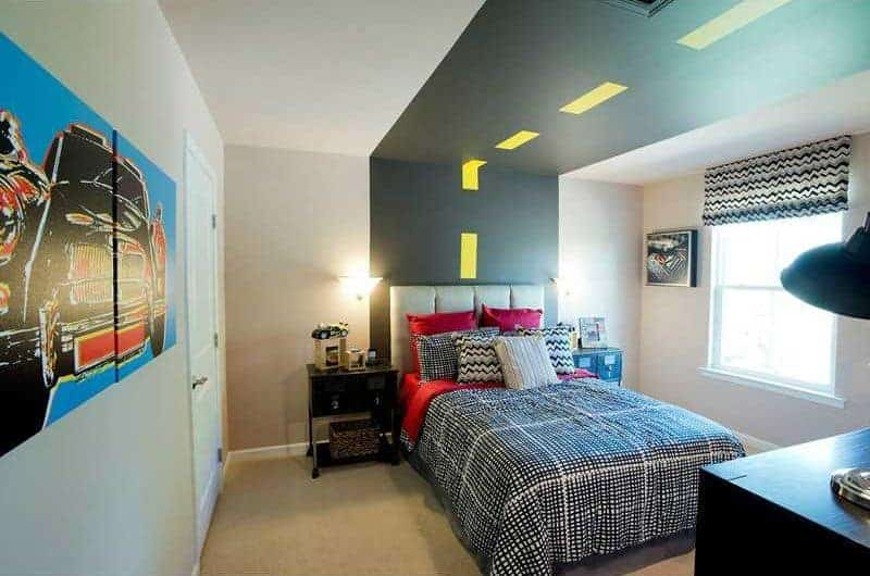 Boy's bedroom with a road track ceiling and carpet flooring complementing with the beige walls mounted with multi-panel artwork. It includes a tufted leather bed flanked by nightstands and glass sconces.
