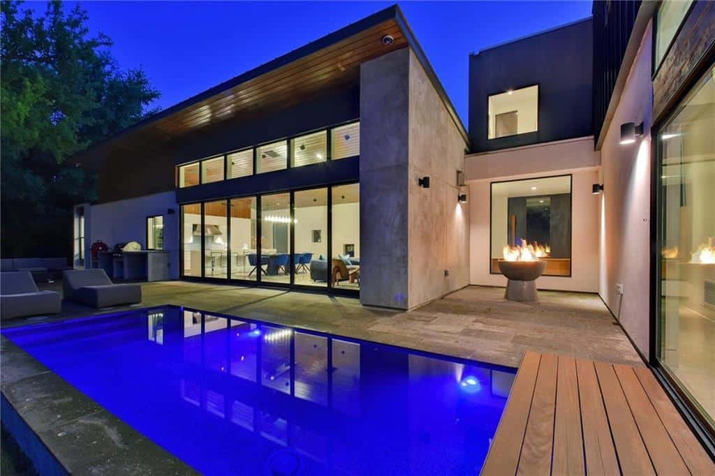 Modern industrial style home with an outdoor firepit and a swimming pool.