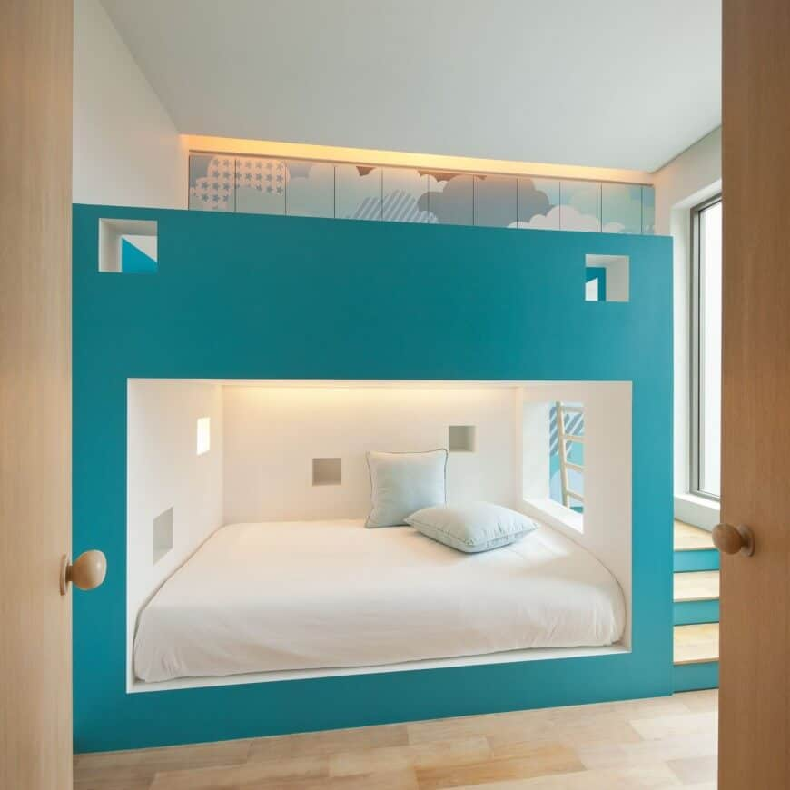 A light wood double door opens to this sleek bedroom featuring a large built-in bunk bed with a teal accent occupying almost the entire space in the room.