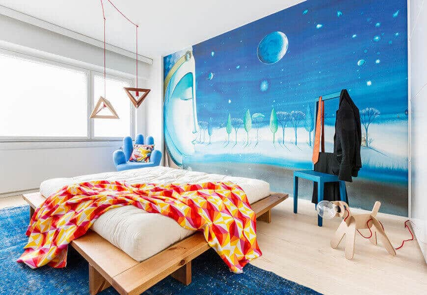 A large scale wall mural sets a serene backdrop to the platform bed in this kids bedroom with a blue high back chair and a hand seat lighted by a pair of wooden triangular pendants.