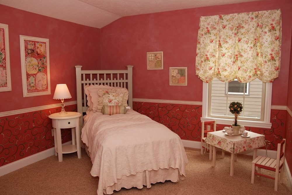 A charming floral valance complements the table mantle in this red bedroom with a skirted bed and round end table topped with a glass table lamp.