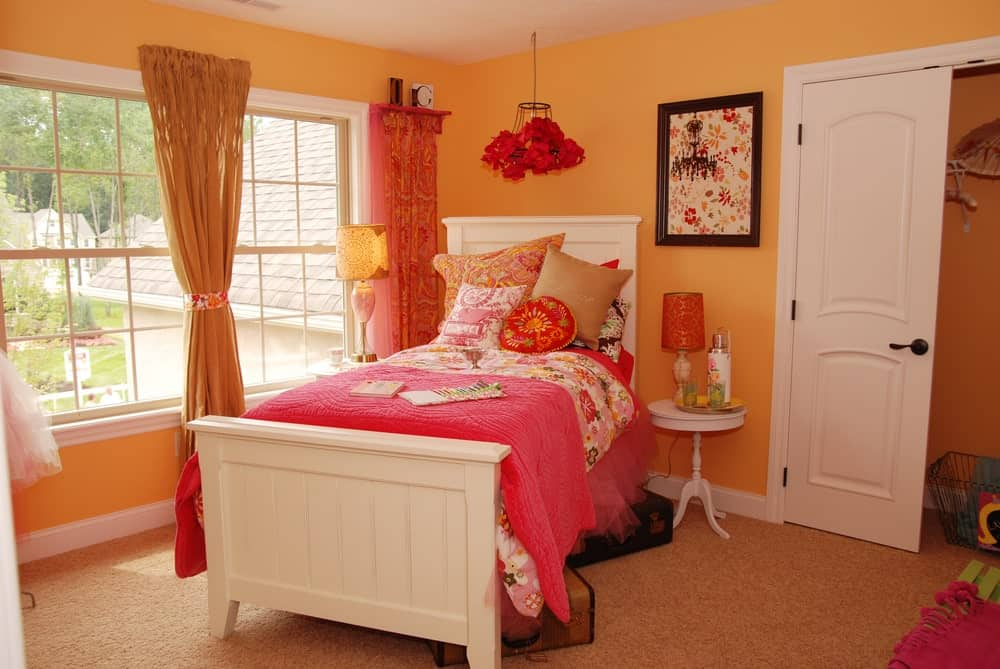 Warm bedroom with gorgeous wall art and a white beadboard bed flanked by round end tables and lampshades. It is illuminated by a floral pendant along with natural light from the white framed windows.